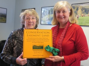 Lora Chatfield (right) and Nancy Jones hold a conserved land sign that will mark Helen's Haven.